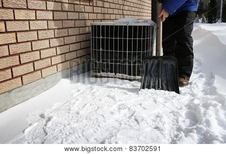 Man shoveling the snow with brick wall and air conditioner on background