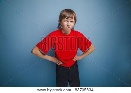 Boy, teenager, twelve years in the red shirt, hands in the side,