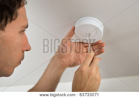 Close-up Of Electrician With Screwdriver Repairing Fire Sensor poster