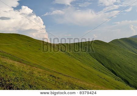 Mountain ridge slopes covered by green grass