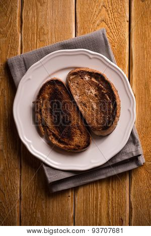 Burnt toast bread on the plate, on wooden table background