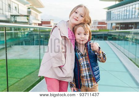 Outdoor portrait of two adorable kids in a city
