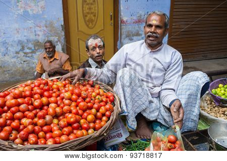 VARANASI, INDIA - 20 FEBRUARY 2015: Grocer puts tomatoes from basket into plastic bag for customer on street market.