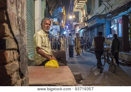 VARANASI, INDIA - 19 FEBRUARY 2015: Indian man sits infront of closed store.