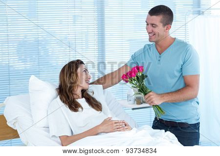 Handsome man offering bouquet of flowers to his pregnant wife in hospital room