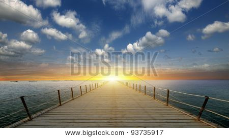 Jetty pointing toward the ocean with dramatic sunset