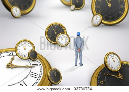Businessman with helmet turning his back to camera against grey background