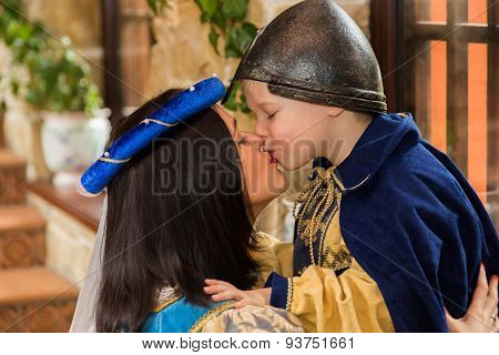 Mother and son in medieval costumes, in a beautiful interior.