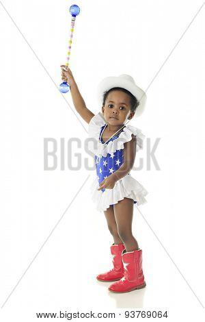 An adorable 2 year old in patriotic attire looking at the viewer as she reaches high with her baton.  On a white background,