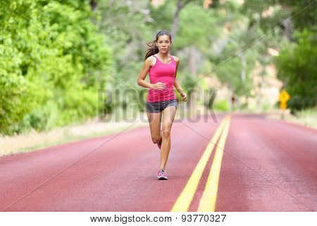 Running fit woman - female runner training outdoors jogging on red road in amazing landscape nature. Fit beautiful fitness model working out outside in summer.