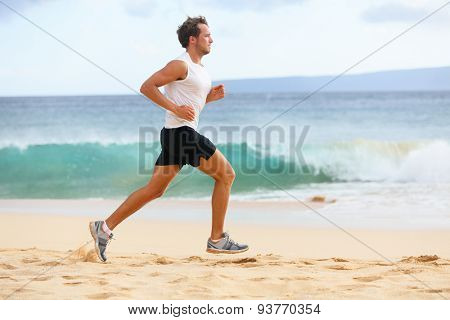 Fitness sports runner man jogging on beach. Handsome young fit sporty male athlete running outside on beautiful beach training. Caucasian male model in his 20s working out in full body length.