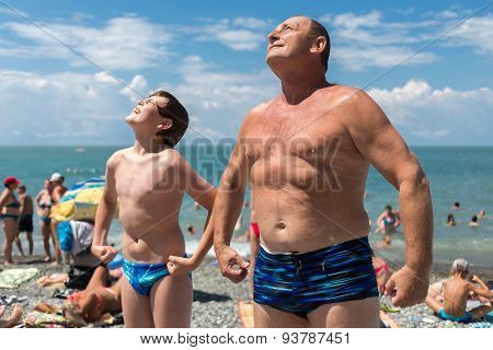Grandfather with his grandson bask in the sun on the beach