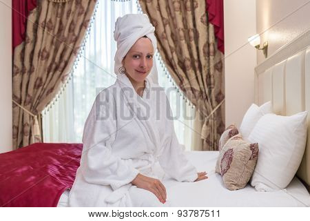 woman in a bathrobe with a towel on her head in a hotel room