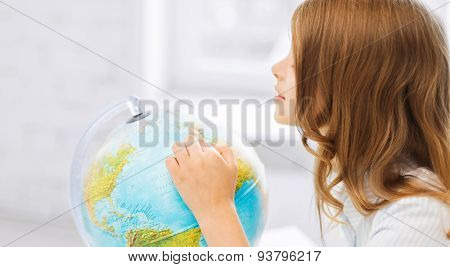 education and school concept - little curious student girl with globe at school
