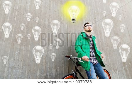 people, startup, inspiration and lifestyle - happy young hipster man with fixed gear bike on city street over concrete wall and lighting bulbs background