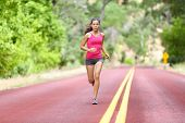Running fit woman - female runner training outdoors jogging on red road in amazing landscape nature. Fit beautiful fitness model working out outside in summer. poster