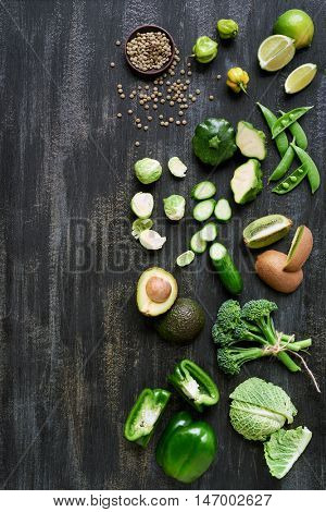 Collection of fresh green vegetables on dark rustic distressed background, avocado, broccoli, lentils, capsicum, peppers, peas, brussels sprouts, kiwi, cucumber with side border