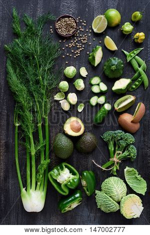 Variety of green vegetables produce on dark background from overhead, broccolini, fennel, avocado, brussel sprouts, kiwi, pepper, peas, lime part of flat lay series