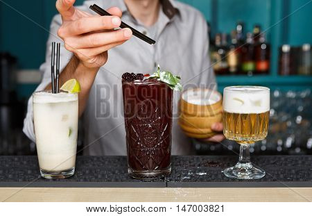 Unrecognizable Barman makes sugar dusting to exotic sweet non-alcoholic cocktails in restaurant. Professional male bartender at work in bar made refreshing drinks. Selective focus on glasses