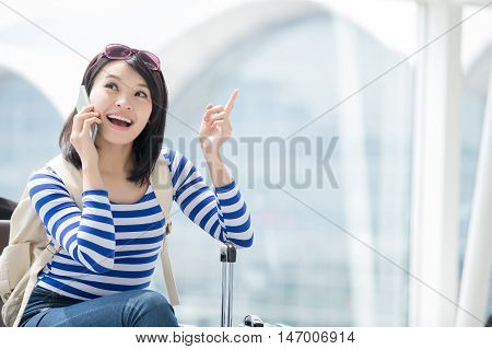 beauty woman is talking the phone happily and show something in hong kong asian