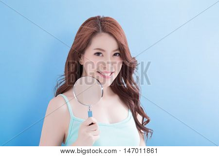 beauty skin care woman take magnifying smile to you with blue background asian