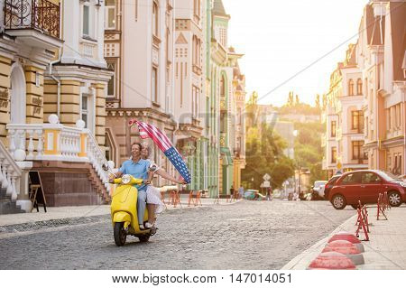 Mature couple riding on scooter. Woman holds flag of USA. Time to ride home. This vacation was unforgettable.