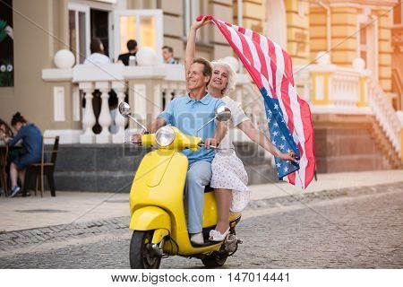 Couple riding scooter and smiling. Mature lady with US flag. Happy citizens of America. Life couldn't be any better.