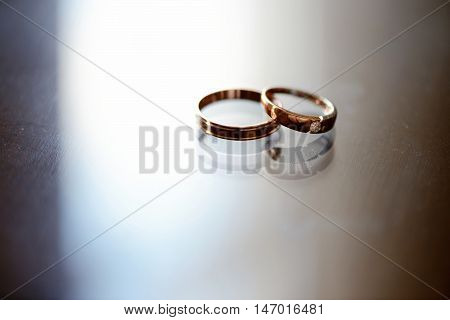 Beautiful wedding rings for bride and groom. Beauty of wedding accessories indoors. Close-up bridal jewel of marriage. Female and male decoration for couple. Jewelry for man and woman