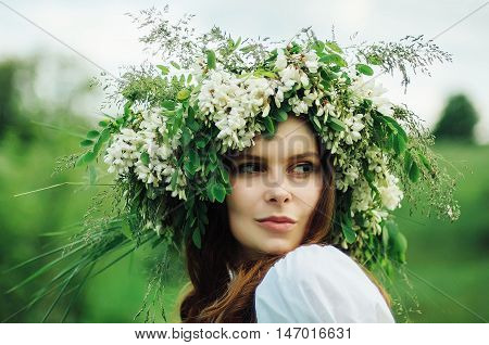 Young pagan Slavic girl conduct ceremony on Midsummer. Beauti girl dressed in a white blouse with embroidery denim shorts boots with grass Acacia wreath on his head against the background of nature poster