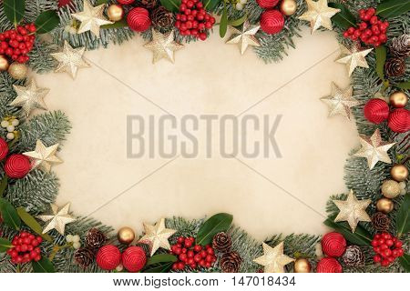 Christmas background border with gold star and red bauble decorations, holly, mistletoe, snow covered spruce fir and pine cones on old parchment paper.