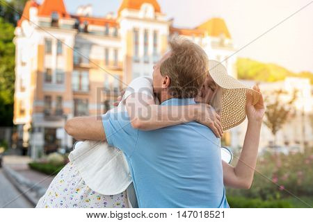 Adult woman hugs man. Couple on city background. Long time no see. I missed you so much.