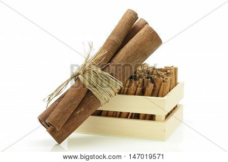 Three cinnamon sticks wrapped together and a wooden crate.