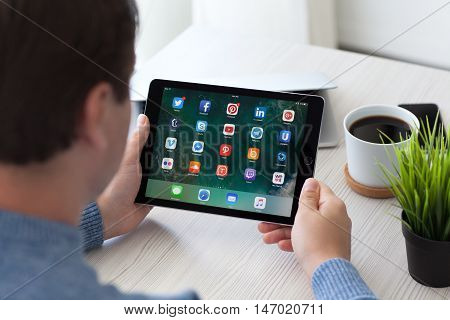 Alushta Russia - September 2 2016: A set of programs from famous brands of social networking on the iPad Pro in man hands. iPad Pro was created and developed by the Apple inc.
