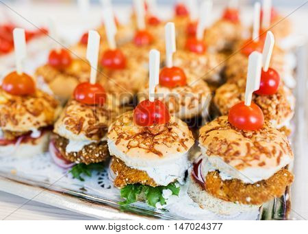 fast food, junk-food, catering and unhealthy eating concept - close up of canape hamburgers or sandwiches on serving tray