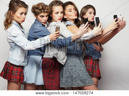 group of young women looking at their smartphones