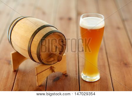 brewery, drinks and alcohol concept - close up of draft lager beer in glass and wooden barrel on table