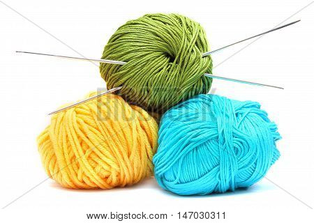 Balls of wool with knitting needles isolated on white background
