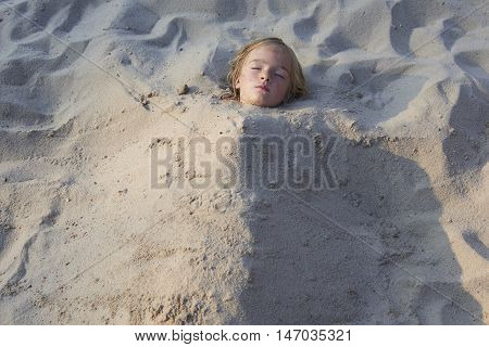 Child blond Girl Buried in the Sand at the Beach