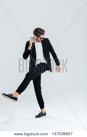 Happy attrative young businessman in black suit listening music with earphones and dancing over gray background