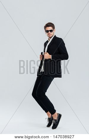 Full length portrait of a serious businessman listening music with earphonea and standing on tiptoe over gray background