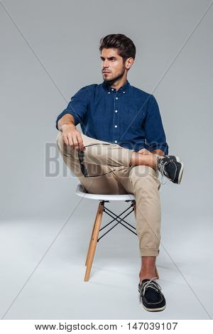 Handsome relaxed man holding suglasses and sitting on the chair over gray background