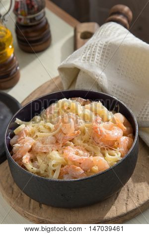 Pasta with shrimps fettucine oil cream and cheese parmesan spices in frying pan
