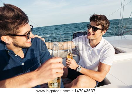 Two young handsome men friends drinking beer while resting on the yacht