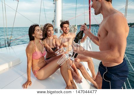 Group of young cheerful happy friends having fun on the yacht and drinking champagne