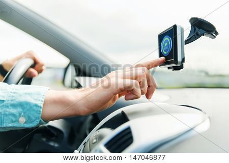 transport, business trip, technology and people concept - close up of male hand pointing to eco mode icon on gadget screen while driving car