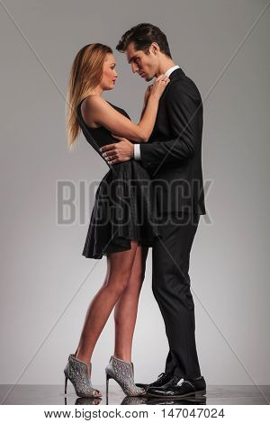 happy elegant couple standing embraced and looking at each other on grey studio background