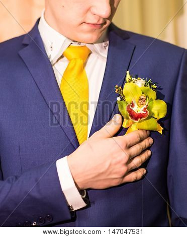 Groom in a suit holding buttonhole. accessories for men