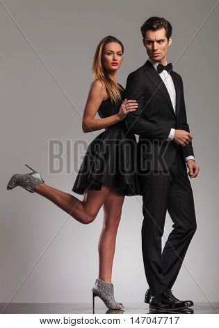 sexy woman in dress holding her man by elbow and her leg up in the air