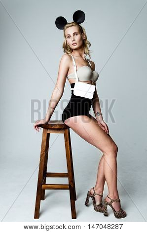 Young attractive woman wearing high waist lingerie with leather black sword belt bag and mouse ears