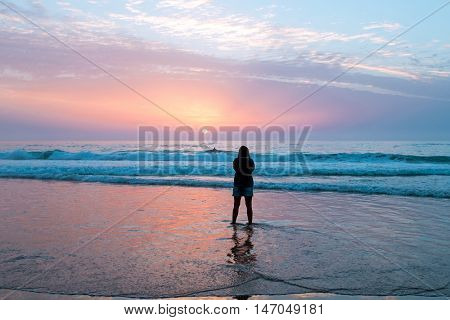 Woman looking at amazing sunset at the westcoast in Portugal